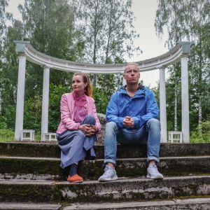 Hannamari Hoikkala ja Nicke Aldén istuvat portailla, taustalla valkoisia pylväitä
