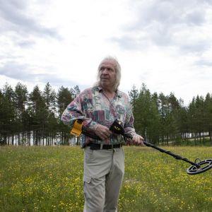 Tapio Rostedt etsimässä vanhaa tsasounaa metallinpaljastimen avulla