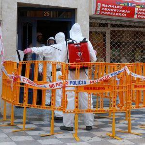 Arbetare i skyddsdräkter utanför en avspärrad bar i Spanien