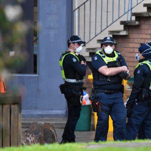 Poliser övervakar ingången till ett bostadskomplex som har isolerats på grund av många coronafall bland invånarna.