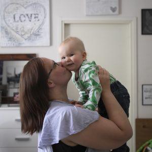 Äiti pitelee lastaan ilmassa ja suutelee hänen poskeaan