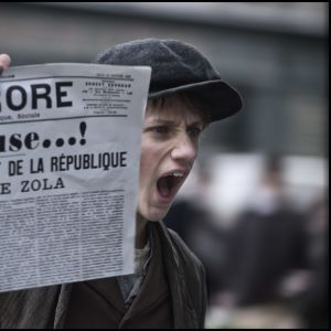 En pojke håller upp tidningen L'Aurore med löpsedelstexten: J'Accuse...!