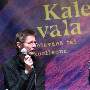 Juha Hurme ja Tuomari Nurmio puhuvat mikrofoneihin Kalevala elävänä tai kuolleena -julisteen edessä.