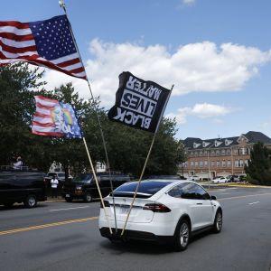 En bil med flaggor kör längs en väg