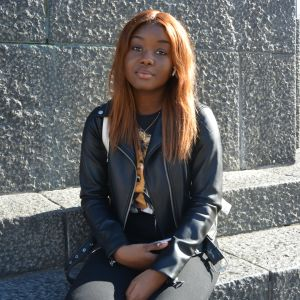 Mörkhyad tonårsflicka med läderjacka sitter vid staty.