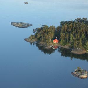 En ö med en röd stuga och blått vatten omkring i Ingå skärgård.