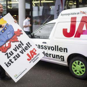 """Mies kantaa kylttiä, jossa lukee """"Liika on liikaa"""" Bruggissa Sveitsissä 22. elokuuta 2020."""