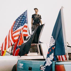 En man omgiven av flaggor står på flaket till en pick-up