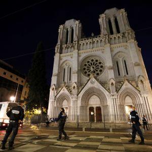 Poliser står framför en belyst kyrka