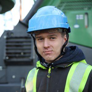 Metsäkoneenkuljettajaksi oppisopimuksella opiskeleva isokyröläinen Kalle Kauppi John Deere harvesterin ääressä