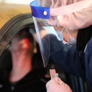 Suojavarusteisiin sonnustautunut sairaanhoitaja ottaa näytettä autossa istuvan henkilön nenästä koronatestipisteellä.