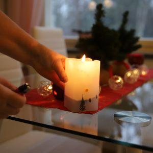 Eija Pekonen kotonaan kynttilä kädessä.