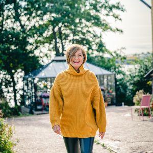 Maria Sundblom Lindberg kommer leende gående mot kameran. Somrig bakgrund med lävträd, växthus och knuten på ett gult trähus.