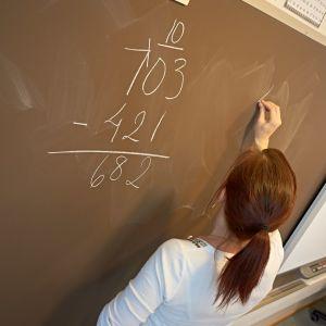 En grundskolelärare skriver på en svart tavla