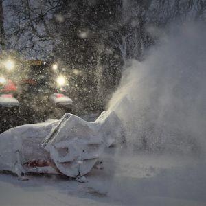 Traktor med snöplog som sprutar snö.