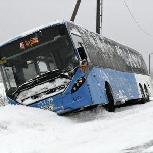 En buss har kört i ett dike på en snöig väg. Bussen är blå och vit och täckt av snö.