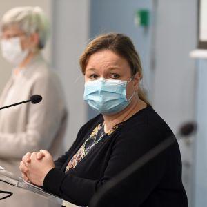 En kvinna klädd i svart kofta och färggrann blus står vid en mikrofon vid ett litet podium. Hon har ett blått munskydd.