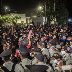 Suuri joukko siirtolaisia lähestyy poliisirivistöä