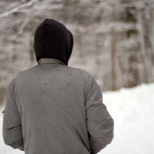 En ung man bakifrån i vinterlandskap.