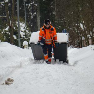Jäteauton kuljettaja vetää roska-astioita lumimössössä.