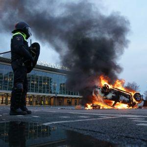 Två kravallutrustade poliser står bredvid en brinnande bil