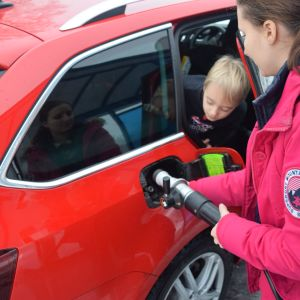 Anna Laima tankar gasbilen medan hennes son ser på.