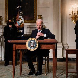 Joe Biden sitter vid ett bord och undertecknar papper. Bredvid honom står två personer.