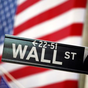 Wall Street-skylt framför USA:s flagga.