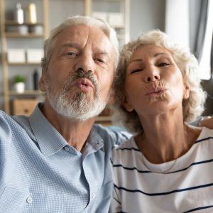 Äldre man och kvinna gör pussmunnar mot kameran