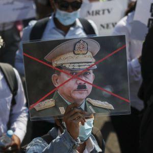 Mielenosoittaja osoittaa mieltään armeijan päällikköä  Min Aung Hlaingi vastaan, jolle on piirretty Hitler-viikset.