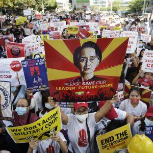 Mielenosoittajat kannattelivat Myanmarin johdosta syrjäytyn Aung San Suu Kyin kuvaa Yangonissa lauantaina.