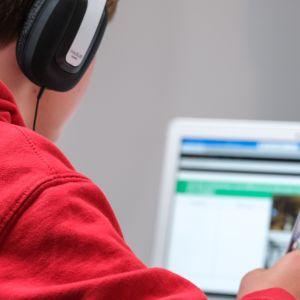 En person sitter vid datorn vid ett bord och gör anteckningar.