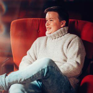 Sami Kieksi istuu punaisella tuolilla ja hymyilee