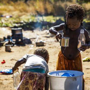 Två barn vid en vattenhink