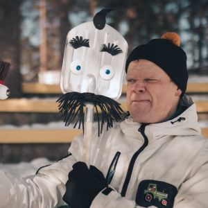 En man i vinteroverall grimaserar mot en kvast och en spade som han håller upp framför sig.