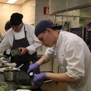 Två unga män i förda kockkläder och handskar lägger upp mat på fat i ett skolkök