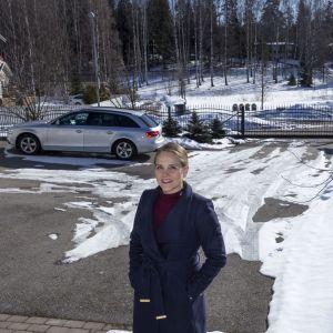 Espoolainen Minna Wallin seisoo etupihallaan. Takana näkyvälle aukealle rakennetaan kerrostaloja.