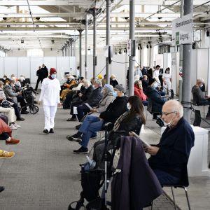 Stor sal där folk väntar på stolar med stort avstånd mellan varandra.