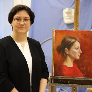 Repin-instituutin amanuenssi Aleksandra Hintsala Risto Paasin maalauksen vieressä.