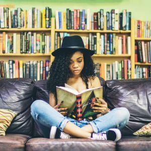 Tyttö istuu sohvalla jalat ristissä ja lukee kirjaa