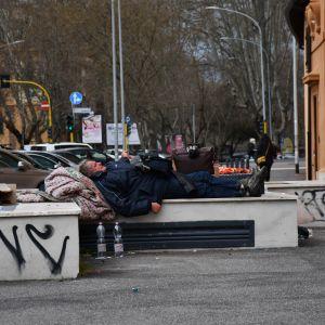 En hemlös man sover på en bänk i Italiens huvudstad Rom