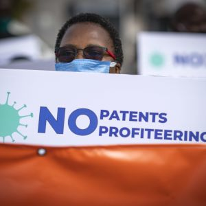 "En demonstrant håller upp ett plaket med texten ""No Patents profiteering"""