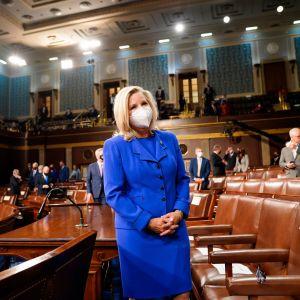 Maski kasvoillaan oleva Liz Cheney seisoo yksin kongressin istuntosalissa.