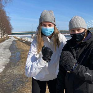 Maskeihin ja talvivaatteisiin sonnustautuneet jääkiekkoilijat Sini Karjalainen (vas) ja Aino Karppinen lumisessa jokirannassa, taustalla Jätkänkynttilän silta.
