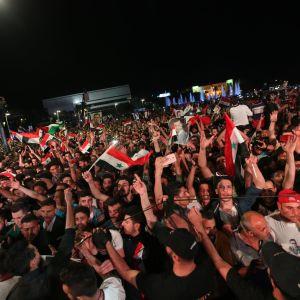 Hundratals människor firar och viftar med syriska flaggor.