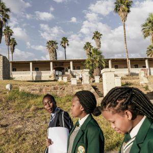 Skolflickor i Namibia Juni 2017. I bakgrunden ett monument till minne av dem som blev offer för det folkmord som Tyskland begick i början av 1900-talet.