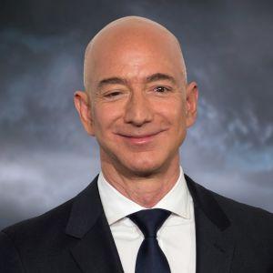 Porträtt av en leende, skallig man i vit skjorta, svart kavaj och mörkblå slips.