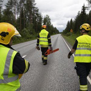 Pelastushenkilökuntaa kävelemässä tiellä moottorisahan kanssa