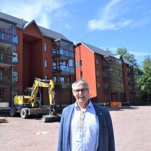 Juha-Pekka Isotupa framför de nya våningshusen i Sjundeå.