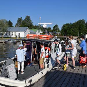Passagerare stiger ombord på taxibåten Diana II i Ingå småbåtshamn.